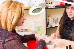 Manikürist Shaping Nails des weiblichen Kunden Stockfoto