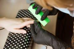 Maniküristpolierzeigefinger für Maniküre im Nagelschönheitssalon Schritt des Maniküreprozesses lizenzfreies stockbild