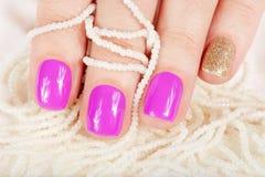 Manikürte Nägel bedeckt mit rosa Nagellack- und Perlenhalsketten Stockfotografie
