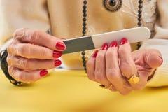 Manikürte Nägel der Frau Archivierung zu  stockbild