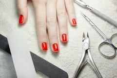 Manikürte rote Nägel mit Nagelwerkzeugen auf weißem Tuch Stockfoto
