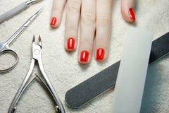 Manikürte rote Nägel mit Nagelwerkzeugen auf weißem Tuch Lizenzfreie Stockfotos