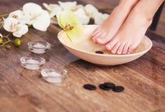 Manikürte weibliche Füße in der hölzernen Schüssel des Badekurortes mit Blumen und Wassernahaufnahme Stockbild