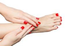 Manikürte weibliche Füße und Hände mit den roten Nägeln lokalisiert auf Weiß Lizenzfreie Stockbilder