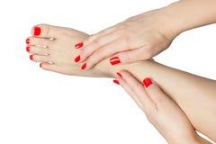 Manikürte weibliche Füße und Hände mit den roten Nägeln lokalisiert auf Weiß Stockfotografie