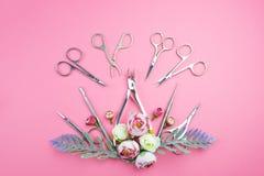 Manik?rewerkzeuge auf einem rosa Hintergrund verziert mit Blumen lizenzfreie stockfotografie