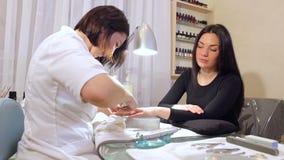 Manik?rist, der H?utchen von den N?geln der Frau mit Nagelscherern entfernt stock video footage