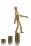 Manikin falling off coin piles Stock Photo