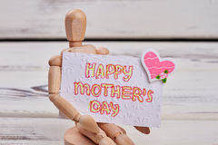 Manikin with greeting card. Royalty Free Stock Image