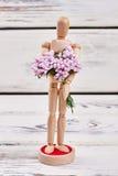 Manikin holding bunch of flowers. Stock Photo
