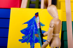 Manikin painting Christmas Tree on canvas Stock Photos