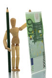 Manikin with pencil and money Stock Images