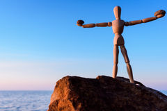 Manikin on the top of boulder. Wooden mannequin on the top of boulder Royalty Free Stock Image