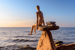 Manikin on the top of stone Stock Photography