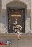 Manikin in traditional costume sitting on a window Royalty Free Stock Photos
