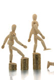 Manikins falling off coin piles Stock Images