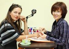 Manikürist bildet Maniküre durch nailfile für Frau Lizenzfreies Stockfoto