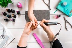Manikyr för klienten Närbild av händerna av en manikyrist och en klient på en träbakgrund Royaltyfri Bild