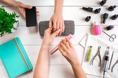Manikyr för klienten Närbild av händerna av en manikyrist och en klient på en träbakgrund Royaltyfria Bilder