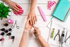 Manikyr för klienten Närbild av händerna av en manikyrist och en klient på en träbakgrund Royaltyfri Fotografi