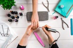 Manikyr för klienten Närbild av händerna av en manikyrist och en klient på en träbakgrund Fotografering för Bildbyråer