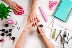 Manikyr för klienten Närbild av händerna av en manikyrist och en klient på en träbakgrund Arkivfoton