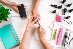Manikyr för klienten Närbild av händerna av en manikyrist och en klient på en träbakgrund Arkivfoto