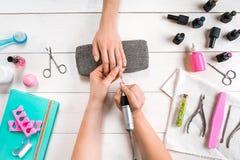Manikyr för klienten Närbild av händerna av en manikyrist och en klient på en träbakgrund Arkivbild