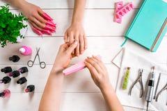Manikyr för klienten Närbild av händerna av en manikyrist och en klient på en träbakgrund Royaltyfria Foton