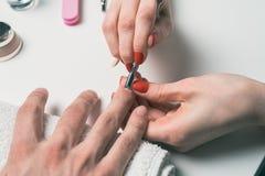manikyr för man` s händer av kosmetologen behandlade nagelbandet av manliga händer genom att använda langaren, skrapa Royaltyfria Bilder