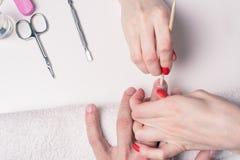 manikyr för man` s händerna av kosmetologen behandlade nagelbandet av händer för man` s genom att använda de orange pinnarna Fotografering för Bildbyråer