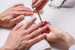 manikyr för man` s kvinnakosmetologen behandlar nagelband av torra manliga händer arkivbilder
