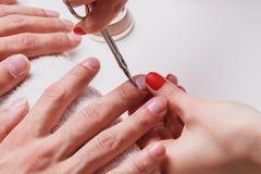 manikyr för man` s kvinnakosmetologen behandlar nagelband av torra manliga händer arkivfoto