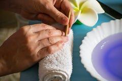 Manikyr hemma Omsorg av nagelbandet, behandling av nagelbandet med en orange pinne royaltyfria foton