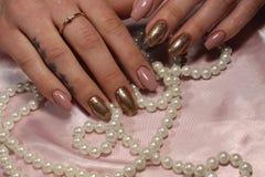 Manikyrdesignbrunt och guld spikar Royaltyfria Foton