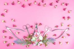 Manikyrhj?lpmedel p? en rosa bakgrund som dekoreras med blommor royaltyfri bild