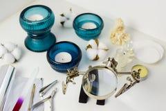 Manikyrhjälpmedel, stearinljus i turkosljusstakar, bomull och keramisk docka, ovanligt förstoringsglas royaltyfria foton