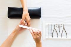 Manikyrist Filing Finger Nails av en kvinna Royaltyfri Fotografi
