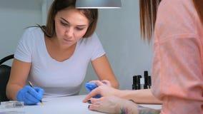 Manikyrist som behandlar klienten på skönhetsalongen - målning på spika Royaltyfri Fotografi