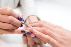Manikyrist som tar bort nagelbandet från flicka för cirkelfinger Royaltyfri Foto
