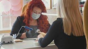 Manikyristen applicerar elkraft spikar mappdrillborren till manikyr på kvinnliga fingrar lager videofilmer