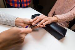 Manikyristen gör manikyrklienten in att spika salongen Fotografering för Bildbyråer