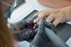 Manikyristen i svarta handskar tar bort stelnar polermedel med en router arkivfoton