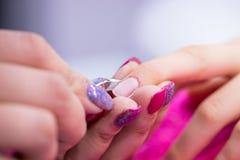 Manikyristen tar bort nagelband från spikar på kvinnors hand arkivfoton