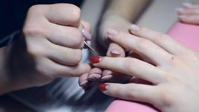 Manikyristmålarfärger spikar med röd färg i salongen lager videofilmer