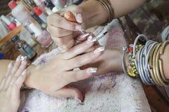 Manikyrprocessen i en danande för visning för skönhetsalong av konstgjort spikar Royaltyfri Fotografi