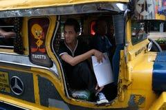 MANILA, FILIPPINE - GENNAIO 25,2012: L'uomo si siede il rotolamento di jeepney Immagine Stock