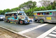 Manila Filippinerna - Februari 3, 2017 Jeepneys spring på en huvudsaklig gata i Manila, Filippinerna Jeepney är ett billigt pris, Arkivbilder