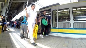 Passengers boarding train at station. Manila, Philippines - August 9, 2016: Passengers are boarding on departing Light Rail Transit Train at station stock footage