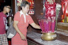 Matured Woman light candle and joss stick to pray for departed relatives in Chinese temple in Manila Royalty Free Stock Images